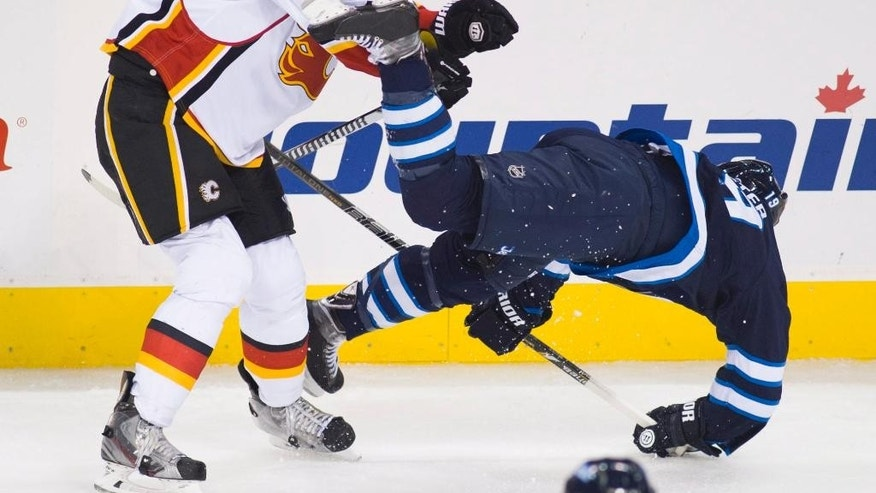 Calgary Flames' Ladislav Smid (15) knocks Winnipeg Jets' Jim Slater (19) to the ice during third-period NHL hockey preseason game action in Winnipeg, Manitoba, Saturday, Oct. 4, 2014. (AP Photo/The Canadian Press, David Lipnowski)