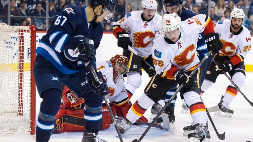Calgary Flames goaltender Jonas Hiller (1) makes the stop as Winnipeg Jets Michael Frolik (67) looks for the puck during second-period NHL hockey preseason game action in Winnipeg, Manitoba, Saturday, Oct. 4, 2014. (AP Photo/The Canadian Press, David Lipnowski)