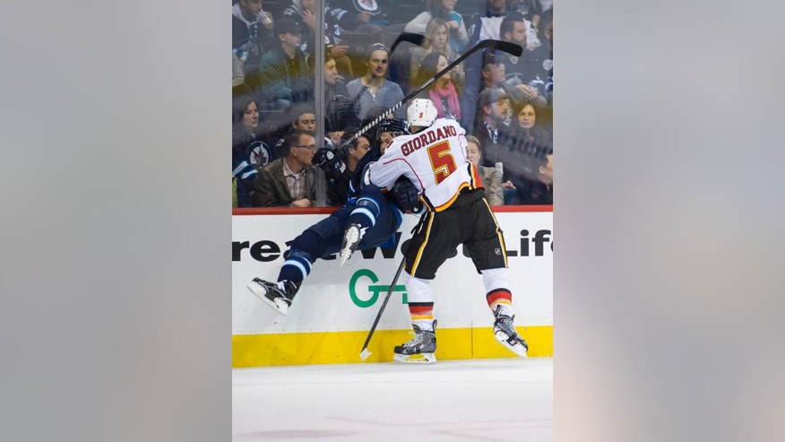 Calgary Flames' Mark Giordano (5) checks Winnipeg Jets' Michael Frolik (67) into the boards during second-period NHL hockey preseason game action in Winnipeg, Manitoba, Saturday, Oct. 4, 2014. (AP Photo/The Canadian Press, David Lipnowski)