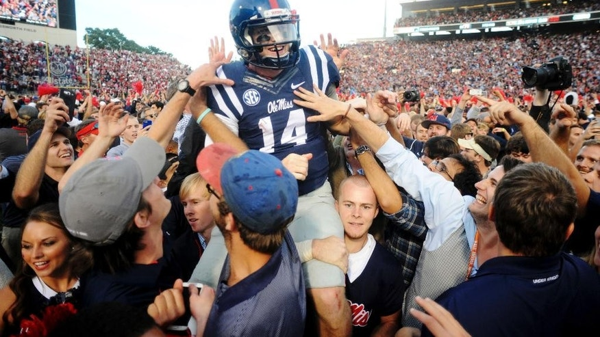 Mississippi  quarterback Bo Wallace (14) is carried off the field by fans following their 23-17 win over No. 3 Alabama in an NCAA college football game in Oxford, Miss., Saturday, Oct. 4, 2014.  (AP Photo/Oxford Eagle, Bruce Newman)