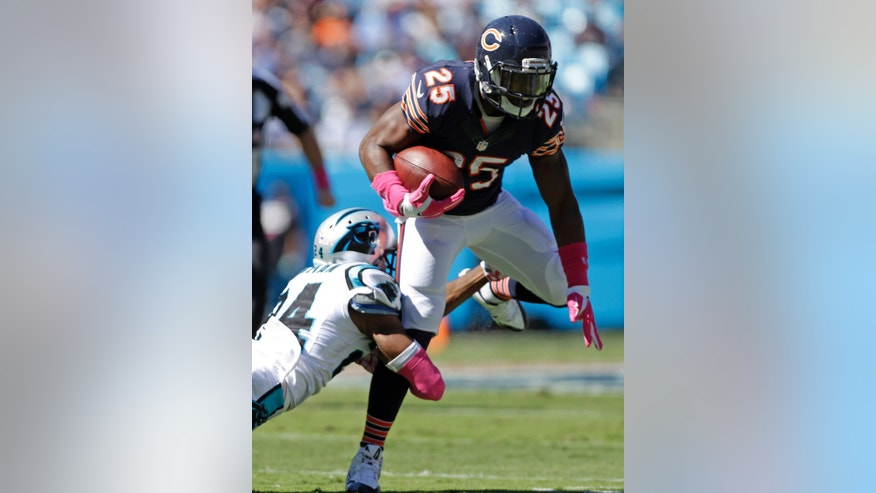 Chicago Bears' Ka'Deem Carey (25) is tackled by Carolina Panthers' Josh Norman (24) during the first half of an NFL football game in Charlotte, N.C., Sunday, Oct. 5, 2014. (AP Photo/Bob Leverone)