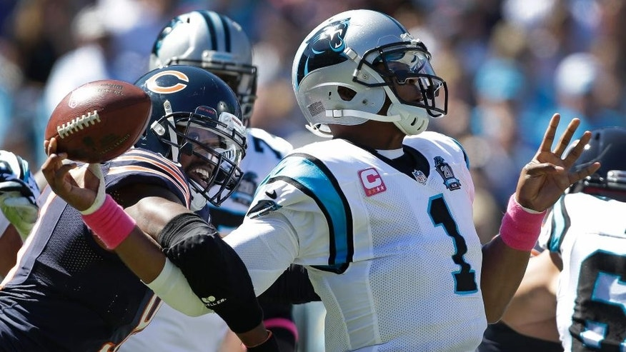 Carolina Panthers' Cam Newton, right, fumbles the ball as he is hit by Chicago Bears' Willie Young, left, during the first quarter of an NFL football game in Charlotte, N.C., Sunday, Oct. 5, 2014. The Bears recovered the ball. (AP Photo/Bob Leverone)