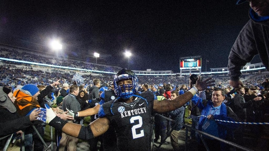 Kentucky defensive end Alvin Dupree celebrates as he leaves the field after Kentucky's defeated South Carolina 45-38 in an NCAA college football game in Lexington, Ky., Saturday, Oct. 4, 2014. (AP Photo/David Stephenson)