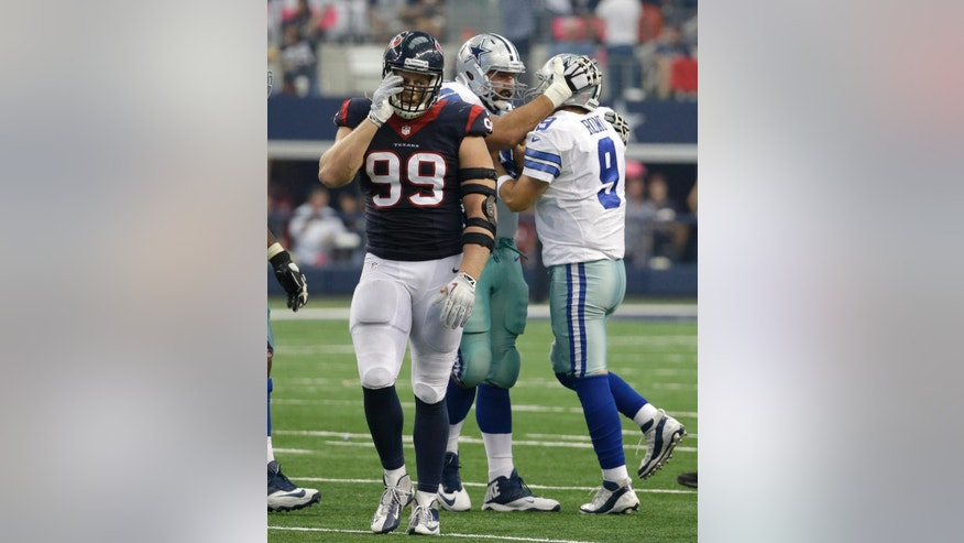 Houston Texans' J.J. Watt (99) walks away as Dallas Cowboys tackle Doug Free, left rear, celebrates a touchdown pass to Terrance Williams by quarterback Tony Romo (9) during the second half of an NFL football game, Sunday, Oct. 5, 2014, in Arlington, Texas. (AP Photo/Tim Sharp)