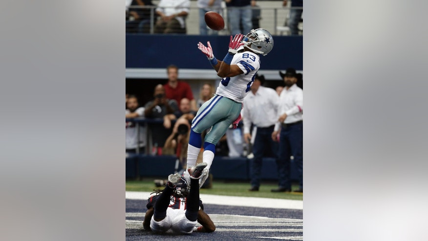 Dallas Cowboys' Terrance Williams (83) reaches up to grab a touchdown pass over Houston Texans' Kendrick Lewis (21) bottom, during the second half of an NFL football game, Sunday, Oct. 5, 2014, in Arlington, Texas. (AP Photo/Brandon Wade)