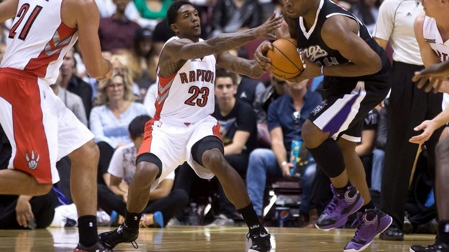 Sacramento Kings' Carl Landry, right, corrals the ball to keep it away from Toronto Raptors' Louis Williams (23) during a pre-season NBA basketball game in Vancouver, British Columbia, Sunday, Oct. 5, 2014. (AP Photo/The Canadian Press, Darryl Dyck)