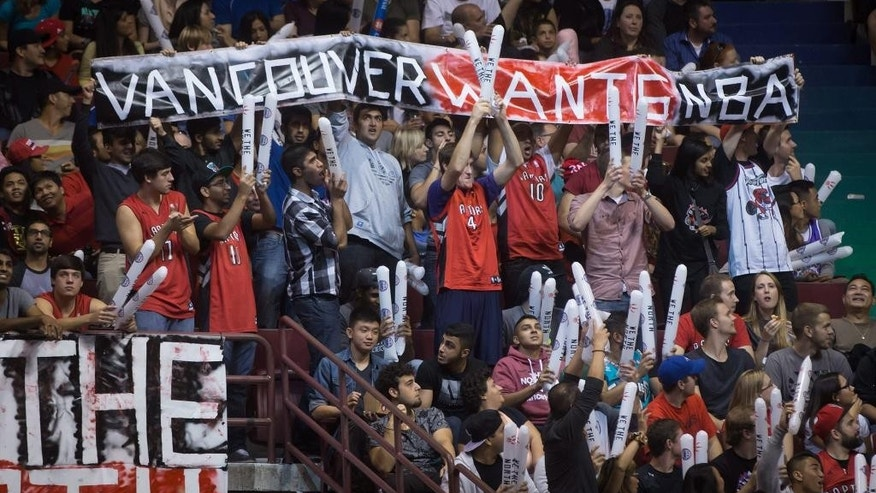 "Fans hold up a sign reading ""Vancouver Wants NBA"" during a pre-season NBA basketball game between the Toronto Raptors and Sacramento Kings in Vancouver, British Columbia, Sunday, Oct. 5, 2014. (AP Photo/The Canadian Press, Darryl Dyck)"