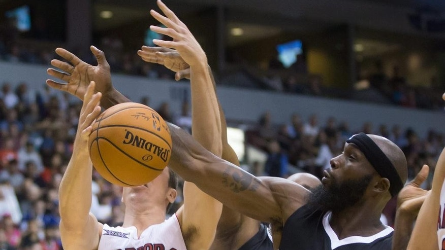 Toronto Raptors' Tyler Hansbrough, left, and Sacramento Kings' Reggie Evans battle for a rebound during the first half of a pre-season NBA basketball game in Vancouver, British Columbia, on Sunday Oct. 5, 2014. (AP Photo/The Canadian Press, Darryl Dyck)