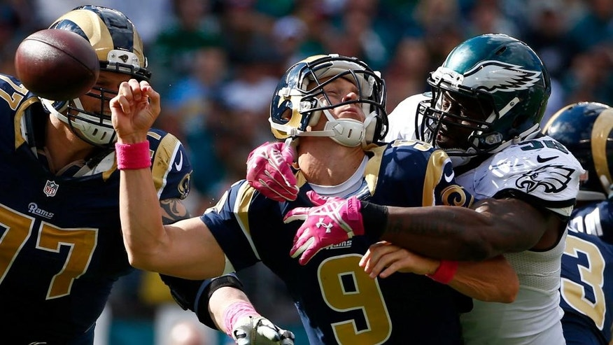 Philadelphia Eagles' Trent Cole, right, knocks the ball loose from St. Louis Rams' Austin Davis (9) during the second half of an NFL football game, Sunday, Oct. 5, 2014, in Philadelphia. Philadelphia recovered the fumble and scored on the play. (AP Photo/Matt Rourke)
