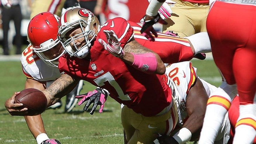 San Francisco 49ers quarterback Colin Kaepernick (7) is tackled by Kansas City Chiefs inside linebacker Josh Mauga (90) and outside linebacker Justin Houston, rear, during the first quarter of an NFL football game in Santa Clara, Calif., Sunday, Oct. 5, 2014. (AP Photo/Marcio Jose Sanchez)