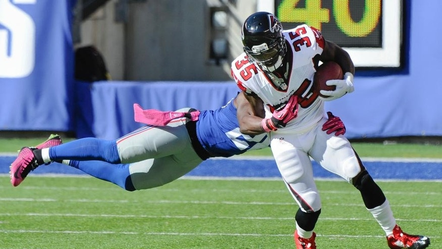 Atlanta Falcons running back Antone Smith, right, avoids the tackle of New York Giants strong safety Antrel Rolle before scoring on a touchdown reception during the second half of an NFL football game, Sunday, Oct. 5, 2014, in East Rutherford, N.J. (AP Photo/Bill Kostroun)