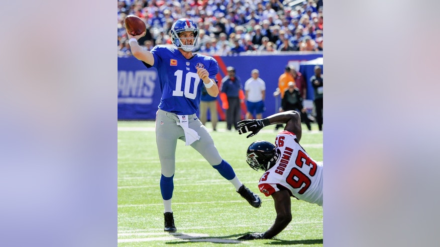 New York Giants quarterback Eli Manning (10) avoids the tackle of Atlanta Falcons defensive end Malliciah Goodman (93) while throwing a pass during the first half of an NFL football game, Sunday, Oct. 5, 2014, in East Rutherford, N.J. (AP Photo/Bill Kostroun)