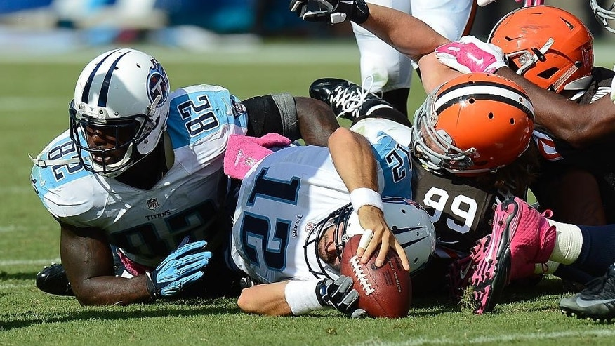 Tennessee Titans quarterback Charlie Whitehurst (12) comes up short as he tries to run for a first down against the Cleveland Browns in the fourth quarter of an NFL football game Sunday, Oct. 5, 2014, in Nashville, Tenn. Defending for Cleveland is Paul Kruger (99). (AP Photo/Mark Zaleski)