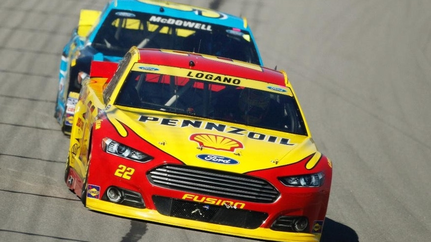NASCAR Sprint Cup Series drivers Joey Logano (22) and Michael McDowell (95) head into turn one during a race at Kansas Speedway in Kansas City, Kan., Sunday, Oct. 5, 2014. (AP Photo/Colin E. Braley)