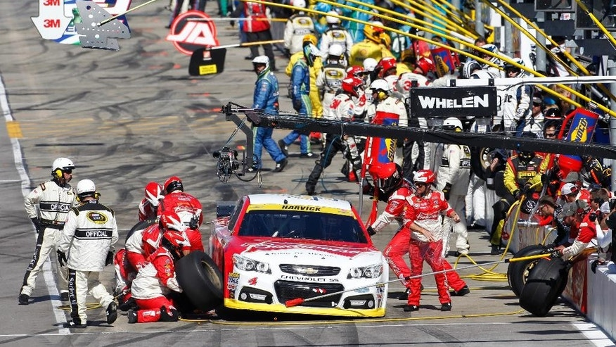 NASCAR Sprint Cup Series driver Kevin Harvick (4) has a tire changed on pit row during a race at Kansas Speedway in Kansas City, Kan., Sunday, Oct. 5, 2014. (AP Photo/Colin E. Braley)