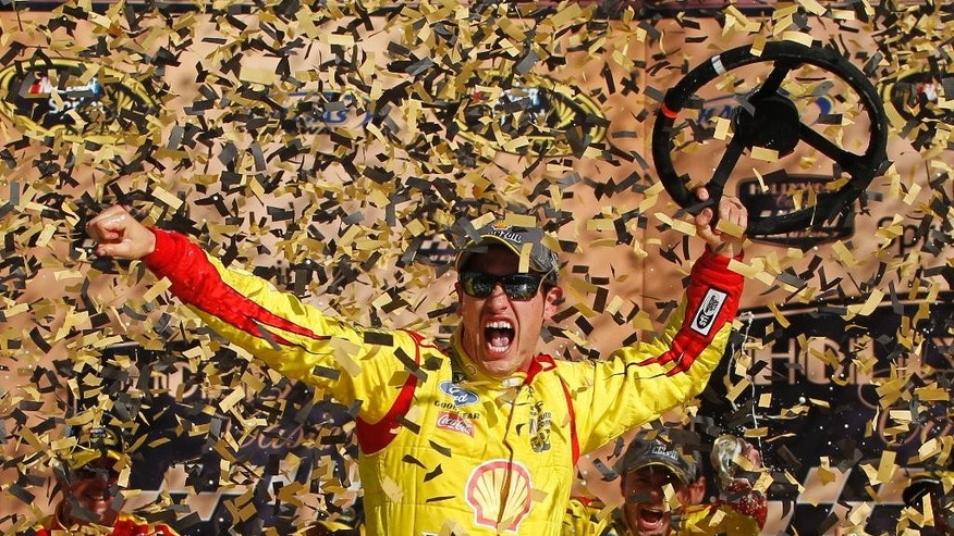 NASCAR Sprint Cup Series driver Joey Logano celebrates his victory in the Hollywood Casino 400 at Kansas Speedway in Kansas City, Kan., Sunday, Oct. 5, 2014. (AP Photo/Colin E. Braley)