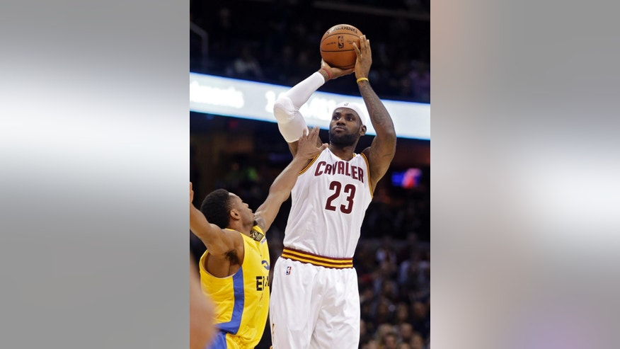 Cleveland Cavaliers' LeBron James (23) shoots a 3-point shot over Maccabi Tel Aviv's Marquez Haynes in the first quarter of a preseason exhibition basketball game Sunday, Oct. 5, 2014, in Cleveland. (AP Photo/Mark Duncan)