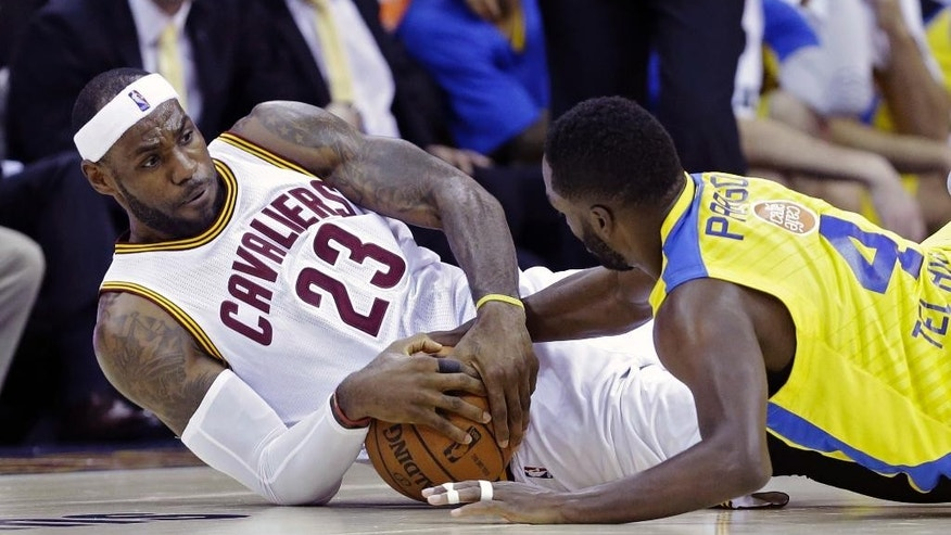 Cleveland Cavaliers' LeBron James (23) fights for a loose ball with Maccabi Tel Aviv's Jeremy Pargo in the second quarter of an exhibition basketball game Sunday, Oct. 5, 2014, in Cleveland. (AP Photo/Mark Duncan)