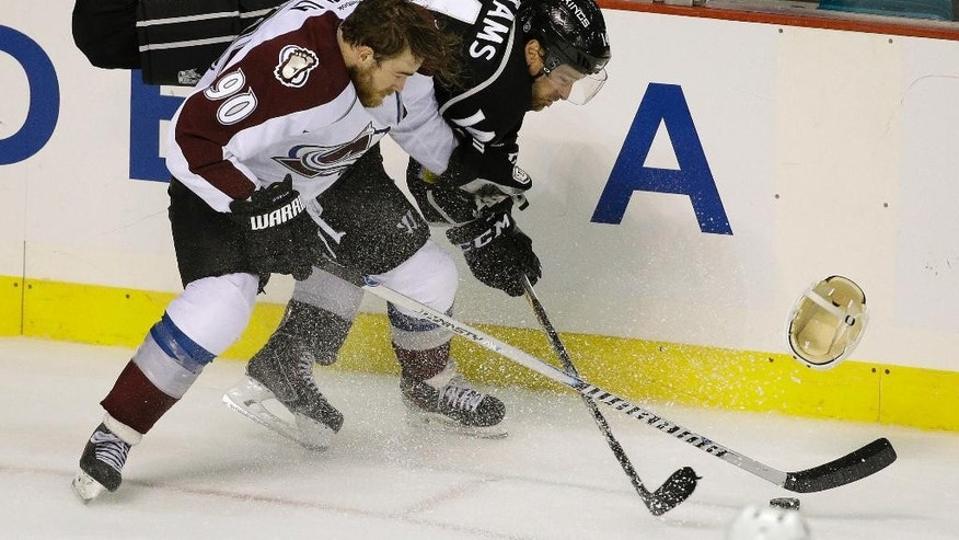 Los Angeles Kings right wing Justin Williams (14) knocks the helmet off Colorado Avalanche center Ryan O'Reilly (90) in the third period of an NHL preseason hockey game Saturday, Oct. 4, 2014, in Las Vegas. Colorado won 3-2 in a shootout. (AP Photo/John Locher)