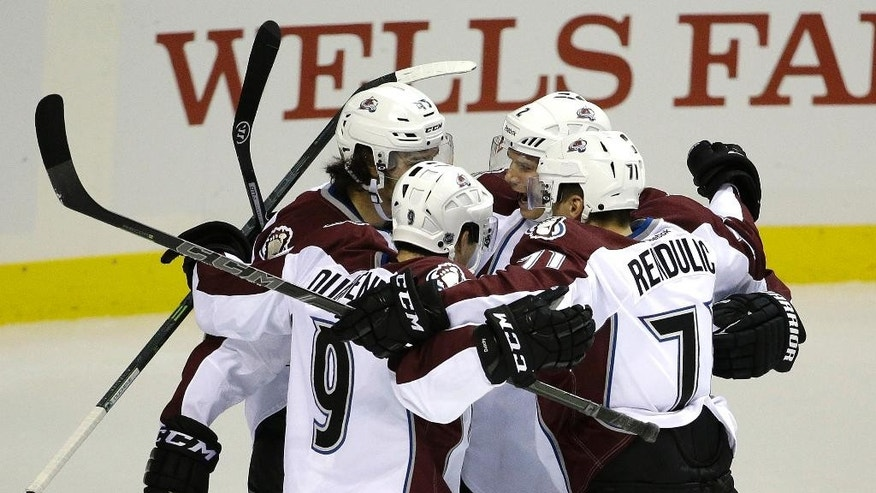 Colorado Avalanche players celebrate after right wing Dennis Everberg, back left, scored in the second period of their NHL preseason hockey game against the Los Angeles Kings on Saturday, Oct. 4, 2014, in Las Vegas. (AP Photo/John Locher)