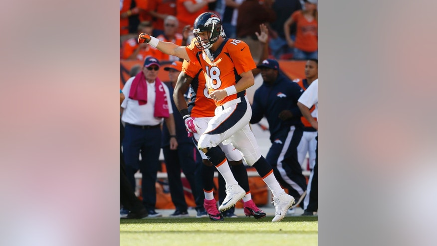 Denver Broncos quarterback Peyton Manning (18) runs upfield after a touchdown pass against the Arizona Cardinals during the second half of an NFL football game, Sunday, Oct. 5, 2014, in Denver. (AP Photo/Joe Mahoney)