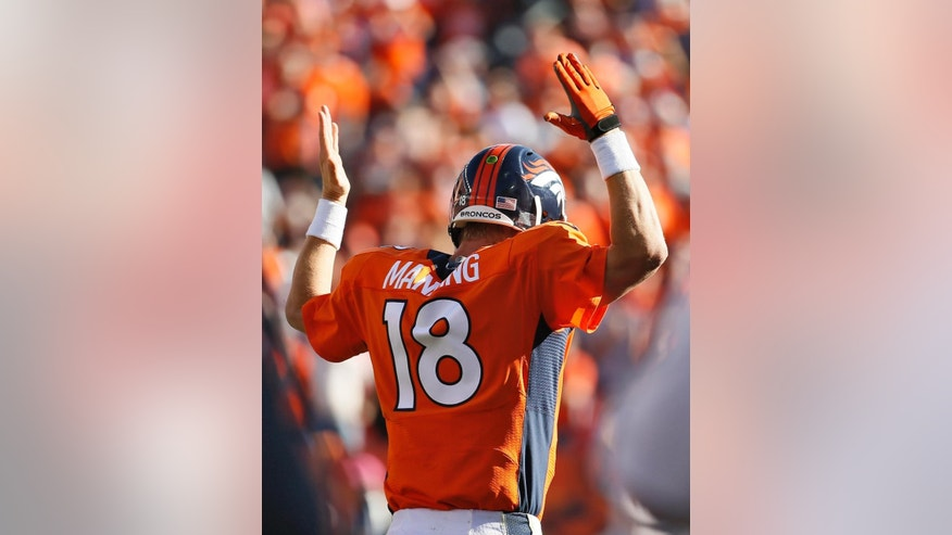 Denver Broncos quarterback Peyton Manning (18) signals a touchdown against the Arizona Cardinals during the second half of an NFL football game, Sunday, Oct. 5, 2014, in Denver. (AP Photo/Jack Dempsey)