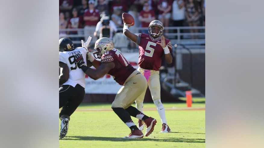 Florida State quarterback Jameis Winston throws for completion as Josue Matias throws a block against Wake Forest's Shelldon Lewinson during the third quarter of an NCAA college football game, Saturday Oct. 4, 2014 in Tallahassee, Fla. Florida State won  43-3. (AP Photo/Steve Cannon)
