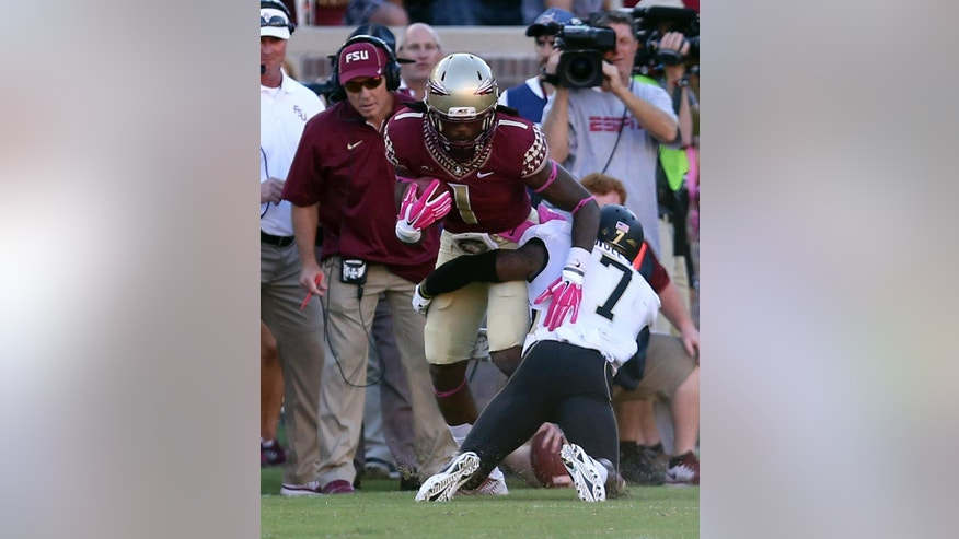 Florida State head coach, Jimbo Fisher, background left, watches Ermon Lane get tackled by Wake Forest's Merrill Noel after picking up a first down in the third quarter of an NCAA college football game, Saturday Oct. 4, 2014 in Tallahassee, Fla. Florida State won the game 43-3. (AP Photo/Steve Cannon)