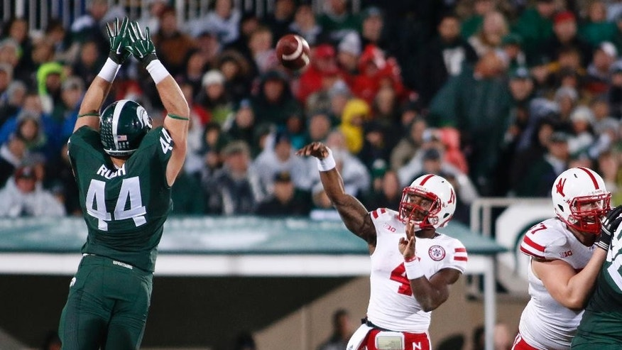 Nebraska quarterback Tommy Armstrong Jr. (4) throws a pass over Michigan State's Marcus Rush (44) as Nebraska's Zach Sterup, right, blocks during the first quarter of an NCAA college football game, Saturday, Oct. 4, 2014, in East Lansing, Mich. (AP Photo/Al Goldis)