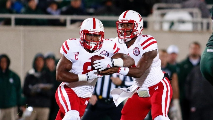 Nebraska quarterback Tommy Armstrong Jr., right, fakes a handoff to Ameer Abdullah against Michigan State during the first quarter of an NCAA college football game, Saturday, Oct. 4, 2014, in East Lansing, Mich. (AP Photo/Al Goldis)