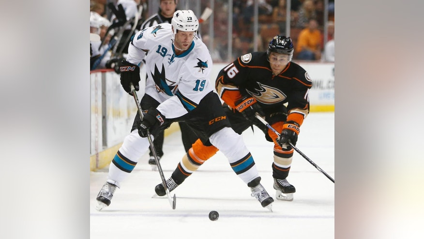 San Jose Sharks center Joe Thornton, left, controls the puck in front of Anaheim Ducks right wing Emerson Etem during the third period of a preseason NHL hockey game in Anaheim, Calif., on Saturday, Oct. 4, 2014. The Ducks won 2-1 in overtime. (AP Photo/Christine Cotter)