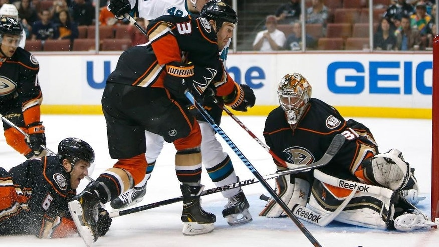 Anaheim Ducks goalie Frederik Andersen (31) watches the puck as defenseman Clayton Stoner (3) keeps the puck out of the reach of San Jose Sharks center Tomas Hertl (48) in the third period of a preseason NHL hockey game in Anaheim, Calif., on Saturday, Oct. 4, 2014. (AP Photo/Christine Cotter)