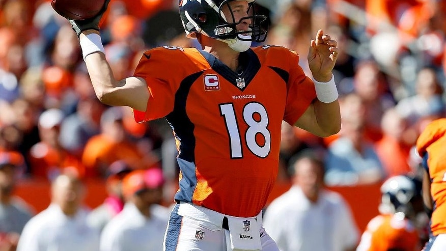 Denver Broncos quarterback Peyton Manning (18) throws against the Arizona Cardinals during the first half of an NFL football game, Sunday, Oct. 5, 2014, in Denver. (AP Photo/Joe Mahoney)