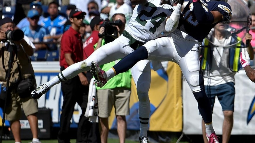 New York Jets defensive back Phillip Adams intercepts a pass intended for San Diego Chargers wide receiver Keenan Allen during the first half of an NFL football game, Sunday, Oct. 5, 2014, in San Diego. (AP Photo/Denis Poroy)