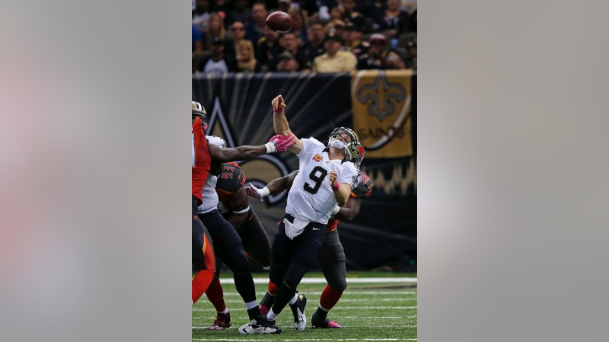 New Orleans Saints quarterback Drew Brees (9) is hit as he throws an interception that was returned for a touchdown in the second half of an NFL football game against the Tampa Bay Buccaneers in New Orleans, Sunday, Oct. 5, 2014. (AP Photo/Bill Haber)