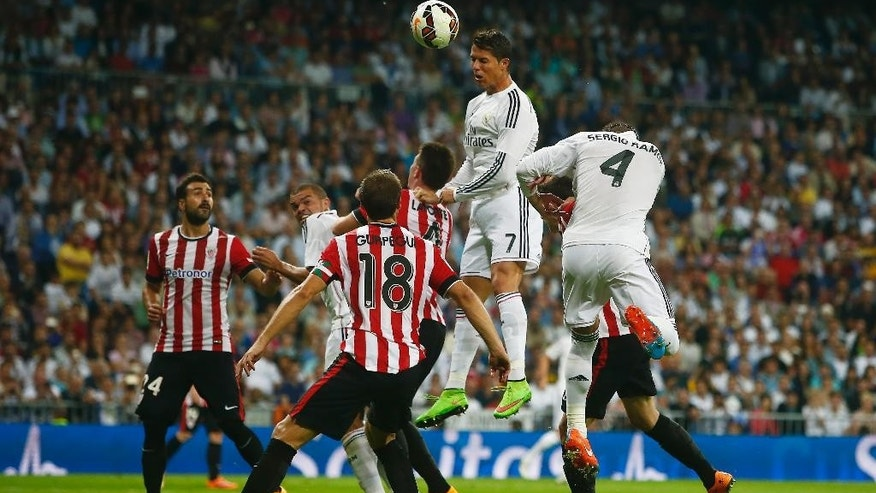 Real's Cristiano Ronaldo, top, hits the ball as he tries to score in between players during a Spanish La Liga soccer match between Real Madrid and Athletic Bilbao at the Santiago Bernabeu stadium in Madrid, Spain, Sunday, Oct. 5, 2014. (AP Photo/Andres Kudacki)