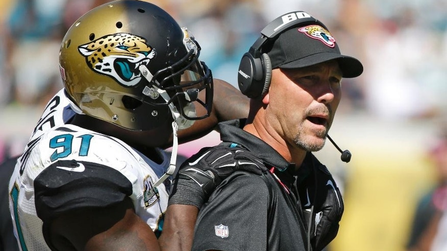 Jacksonville Jaguars defensive end Chris Clemons (91) holds back Jacksonville Jaguars head coach Gus Bradley as Bradley is upset over what he thought should have been pass interference by the Pittsburgh Steelers during the second half of an NFL football game in Jacksonville, Fla., Sunday, Oct. 5, 2014. Pittsburgh won the game 17-9. (AP Photo/Stephen B. Morton)