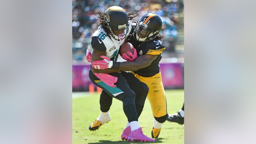 Jacksonville Jaguars running back Denard Robinson (16) is tackled by Pittsburgh Steelers inside linebacker Sean Spence (51) during the first half of an NFL football game in Jacksonville, Fla., Sunday, Oct. 5, 2014. (AP Photo/Phelan M. Ebenhack)