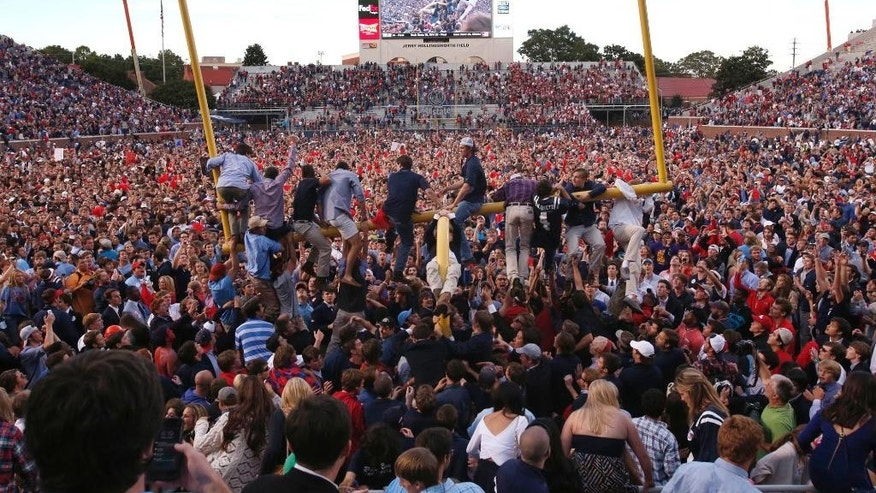 Mississippi fans gather on the field, while a few climb onto a goal post, after Mississippi defeated Alabama 23-17 in an NCAA college football game in Oxford, Miss., on Saturday Oct. 4, 2014. (AP Photo/Tuscaloosa News, Robert Sutton)