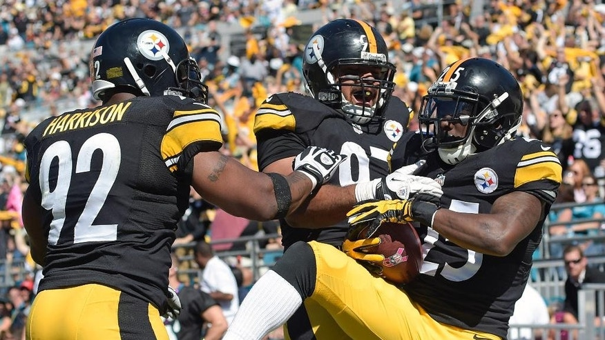 Pittsburgh Steelers cornerback Brice McCain, right, celebrates with teammates James Harrison (92) and Cameron Heyward, center, after he intercepted a Jacksonville Jaguars pass and ran it back for a touchdown during the second half of an NFL football game in Jacksonville, Fla., Sunday, Oct. 5, 2014. (AP Photo/Phelan M. Ebenhack)
