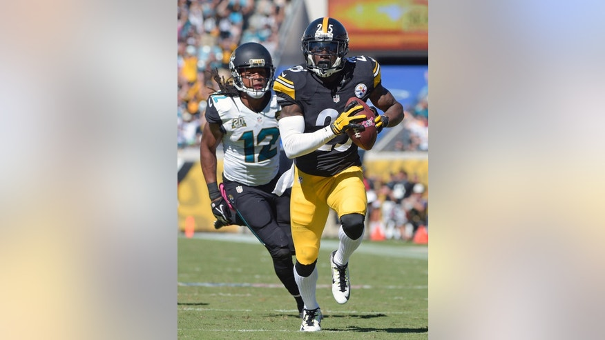Pittsburgh Steelers cornerback Brice McCain, right, returns an intercepted pass 22-yards for a touchdown in front of Jacksonville Jaguars wide receiver Mike Brown (12) during the second half of an NFL football game in Jacksonville, Fla., Sunday, Oct. 5, 2014. (AP Photo/Phelan M. Ebenhack)