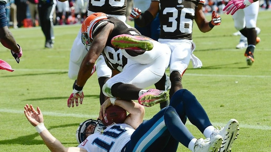 Tennessee Titans quarterback Jake Locker (10) is hit by Cleveland Browns linebacker Christian Kirksey (58) as Locker scores a touchdown on an 11-yard run in the second quarter of an NFL football game Sunday, Oct. 5, 2014, in Nashville, Tenn. (AP Photo/Mark Zaleski)