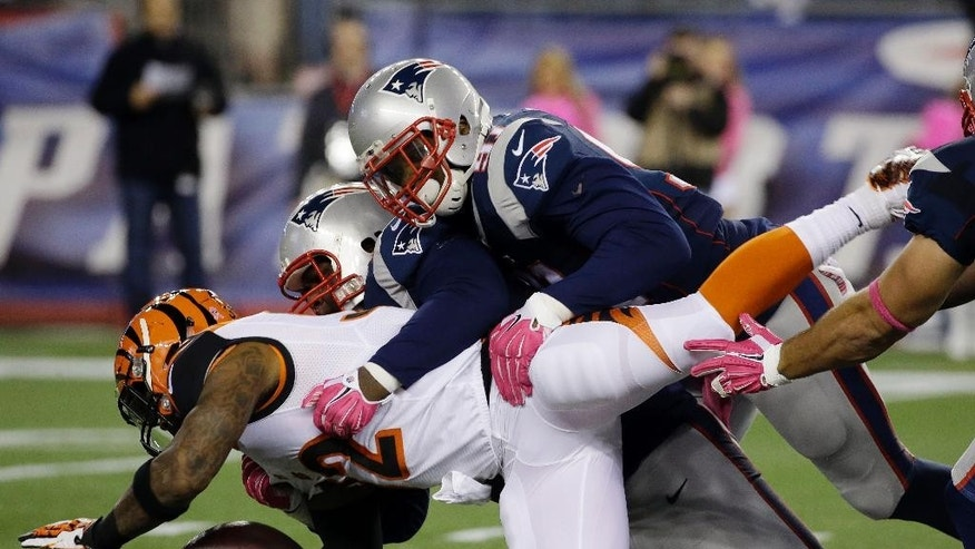 New England Patriots defenders Jamie Collins, top, and Casey Walker, rear, tackle Cincinnati Bengals running back Jeremy Hill (32) in the first half of an NFL football game Sunday, Oct. 5, 2014, in Foxborough, Mass. (AP Photo/Stephan Savoia)