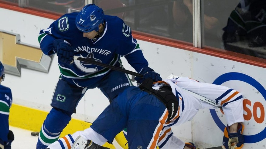 Vancouver Canucks' Shawn Matthias, left, checks Edmonton Oilers' Bogdan Yakimov, of Russia, during the first period of a preseason NHL hockey game in Vancouver, British Columbia, on Saturday, Oct. 4, 2014.  (AP Photo/The Canadian Press, Darryl Dyck)