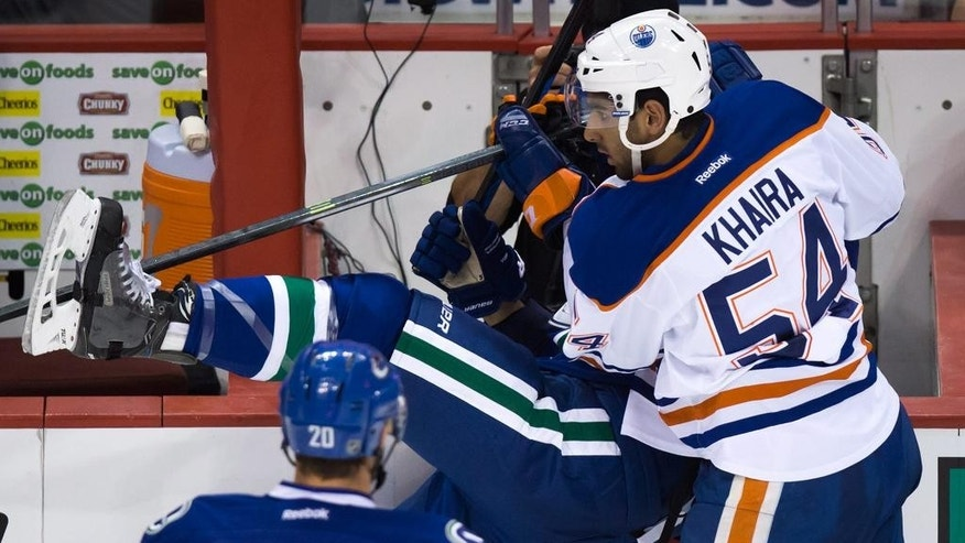 Edmonton Oilers' Jujhar Khaira, right, checks Vancouver Canucks' Luca Sbisa, of Switzerland, during the first period of a preseason NHL hockey game in Vancouver, British Columbia., on Saturday, Oct. 4, 2014. (AP Photo/The Canadian Press, Darryl Dyck)