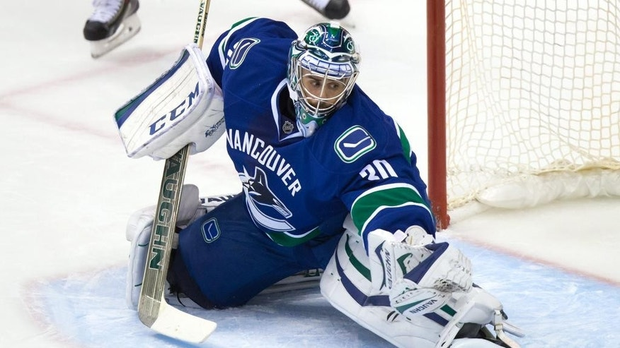 Vancouver Canucks goalie Ryan Miller stretches to make a save against the Edmonton Oilers during the first period of a preseason NHL hockey game in Vancouver, British Columbia., on Saturday, Oct. 4, 2014. (AP Photo/The Canadian Press, Darryl Dyck)