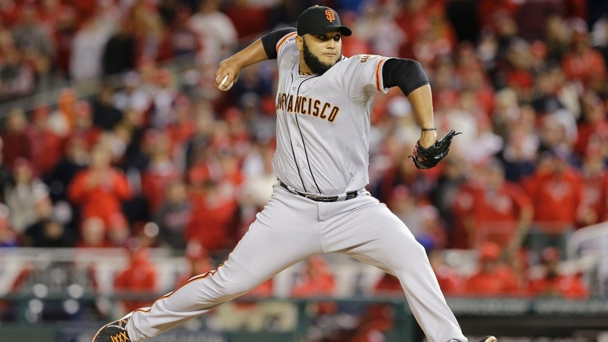 San Francisco Giants relief pitcher Yusmeiro Petit (52) throws in the 12th inning of Game 2 of baseball's NL Division Series against the Washington Nationals in Nationals Park, Saturday, Oct. 4, 2014, in Washington. (AP Photo/Patrick Semansky)