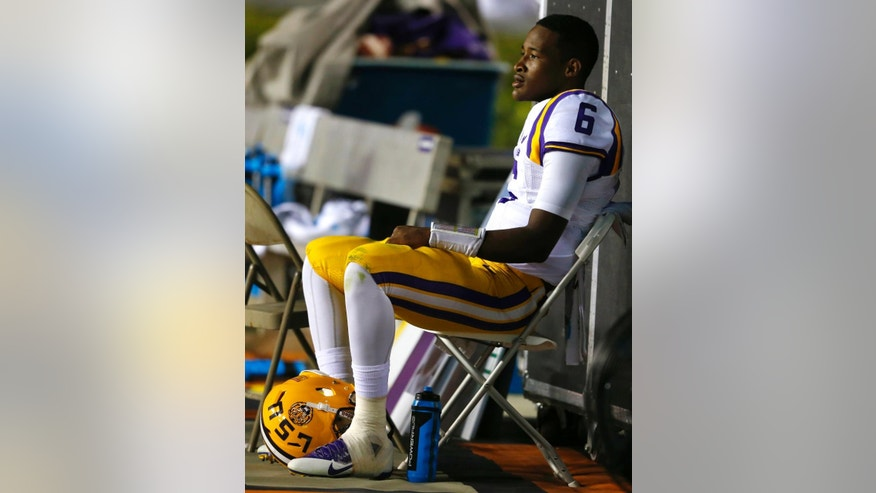 LSU quarterback Brandon Harris (6) sits on the sidelines during the second half of an NCAA college football game as Auburn moves the ball down the field Saturday, Oct. 4, 2014, in Auburn, Ala. (AP Photo/Butch Dill)