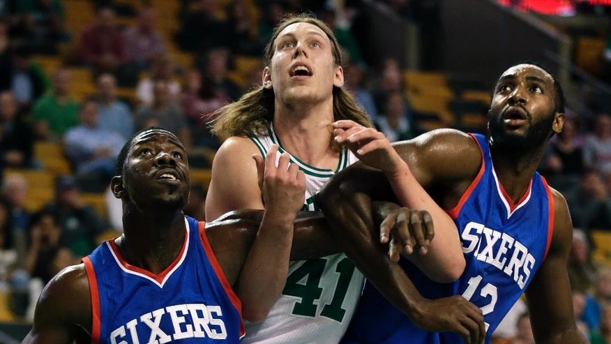 Philadelphia 76ers guard Elliot Williams, left, and forward Luc Richard Mbah a Moute, right,  block out Boston Celtics center Kelly Olynyk on a rebound during the first quarter of a preseason NBA basketball game in Boston, Monday, Oct. 6, 2014. (AP Photo/Charles Krupa)