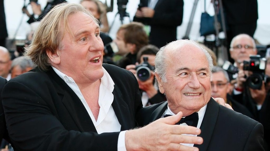 "FILE - This is a Sunday, May 18, 2014 file photo of  FIFA President Sepp Blatter, right, and actor Gerard Depardieu as they pose for photographers as they arrive for the screening of The Homesman at the 67th international film festival, Cannes, southern France. Funded with $27 million of FIFA money, the movie ""United Passions"" is acquiring almost mythical status in football circles. Mythical in the sense that the film, which was shown at the Zurich Film Festival on Sunday, has not been seen by many, and its relationship to documentary truth about FIFA's troubled recent history is loose. In industry circles, ""United Passions"" would easily be defined as a box office flop _ even with star power from Gerard Depardieu, Sam Neill and Tim Roth. (AP Photo/Alastair Grant, File)"